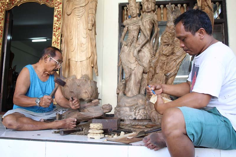 Father and son carving wood buddha statues
