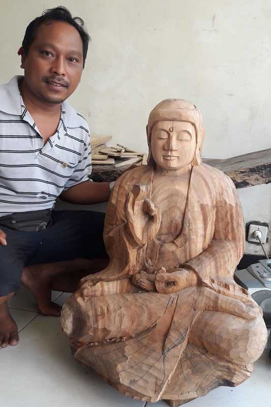 His sons working on a wooden Buddha carving