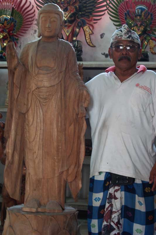 Wayan standing besides an unfinished wood buddha statue
