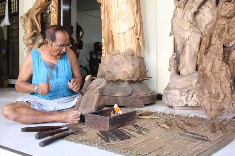 Wayan Carving a Buddha statue in Bali